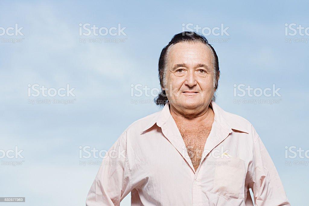 Senior man in a pink shirt stock photo