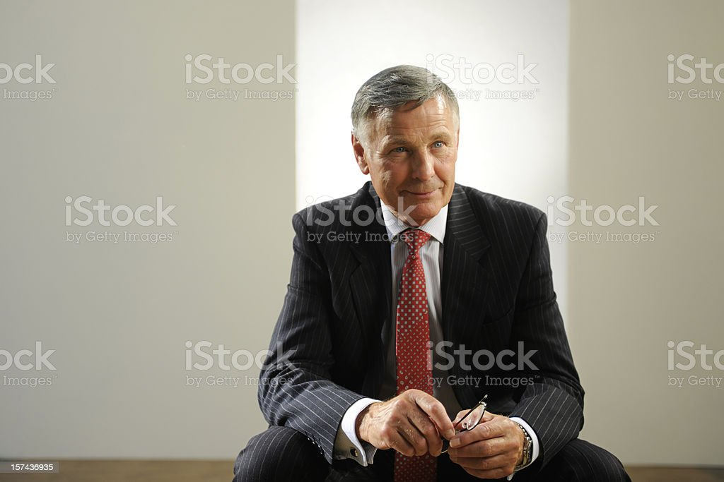 Senior man in a suit grinning at the camera royalty-free stock photo