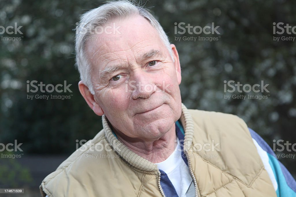 A senior man in a tan vest smiling royalty-free stock photo