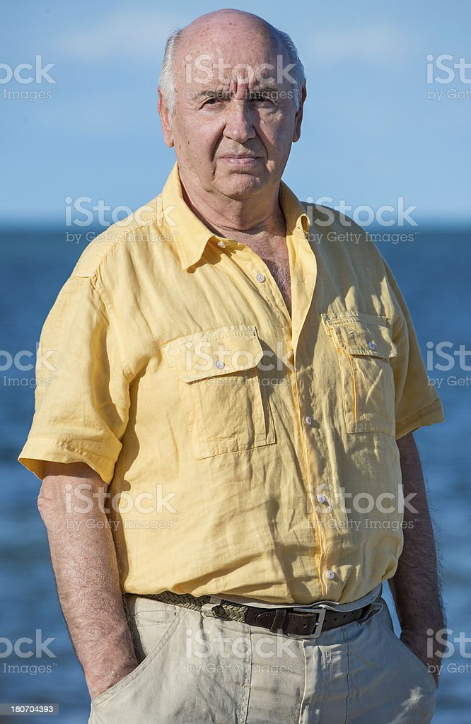 senior man in a yellow shirt at the beach royalty-free stock photo