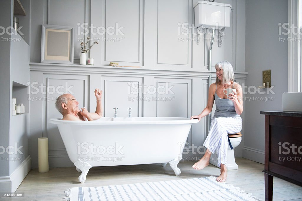 Senior man in bath talking to wife in hotel bathroom stock photo