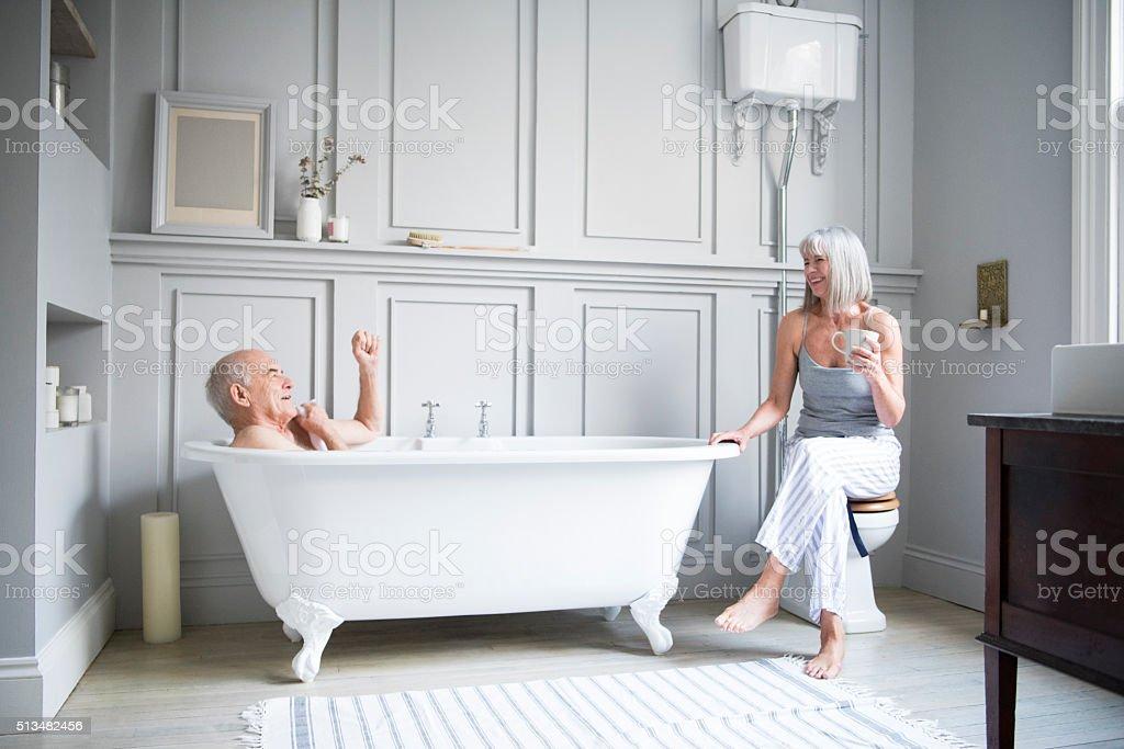 Senior man in bath talking to wife in hotel bathroom stock photo