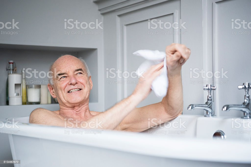 Senior man in bath washing himself smiling stock photo