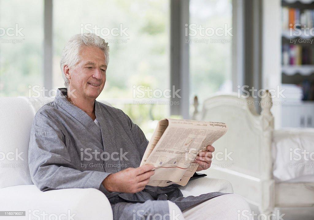 Senior man in bathrobe reading newspaper royalty-free stock photo