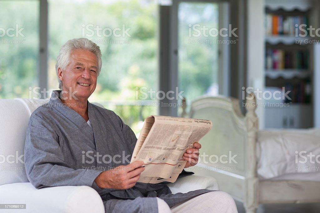 Senior man in bathrobe reading newspaper stock photo