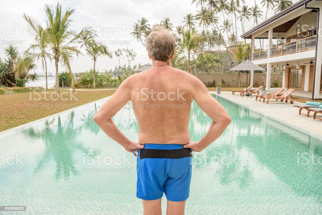 Senior man in blue trunks by pool, rear view stock photo