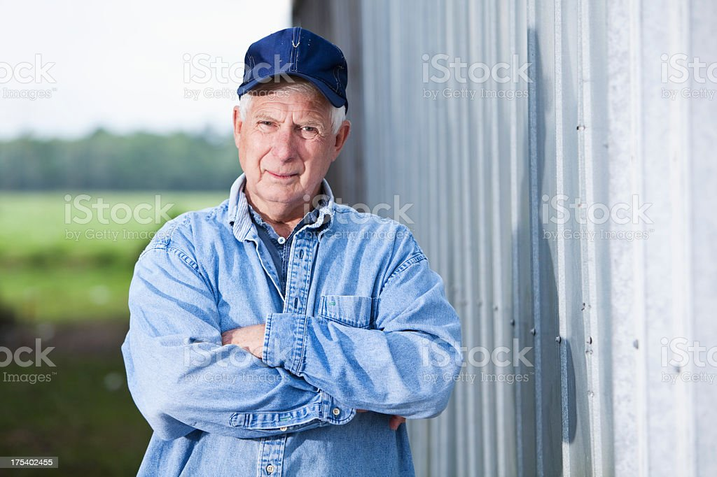 Senior man in cap standing  outside building stock photo