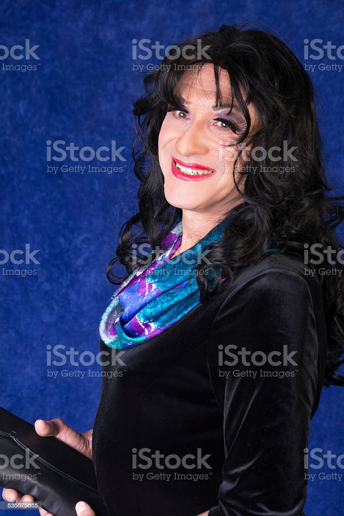 Senior man in drag with makeup, wig and black dress. stock photo