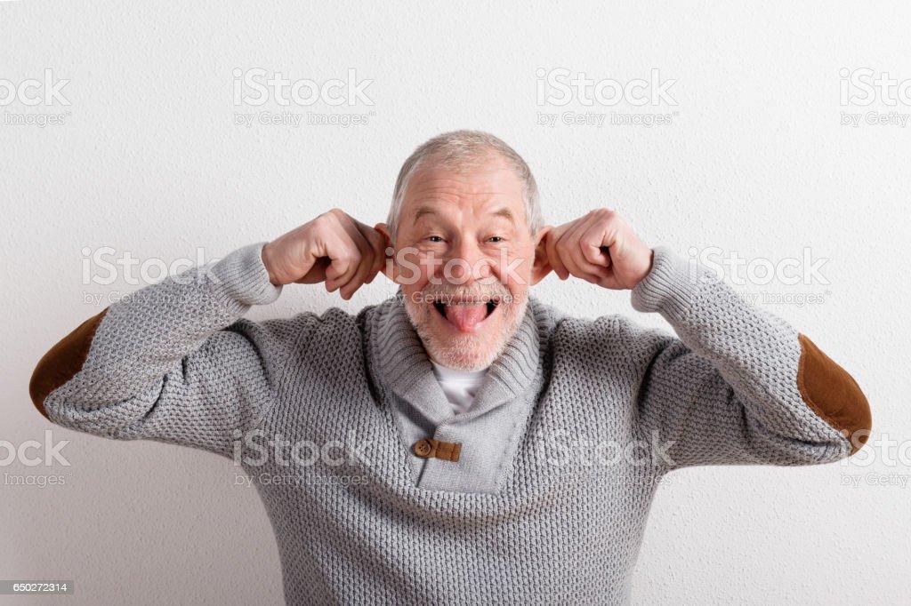 Senior man in gray woolen sweater, studio shot. stock photo