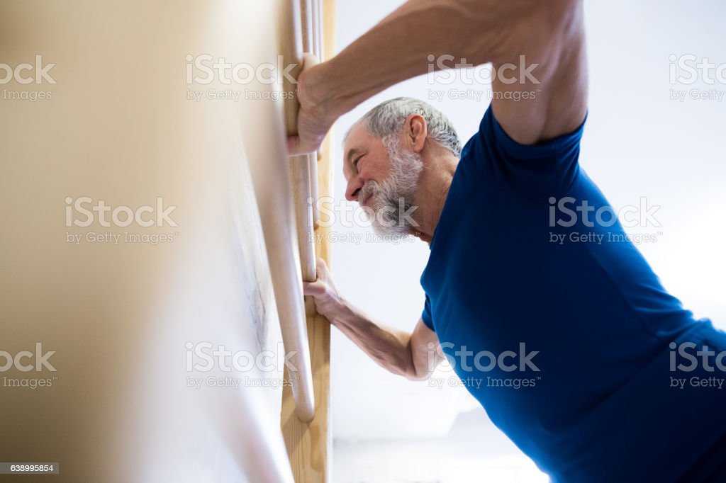 Senior man in gym exercising on wall bars. stock photo