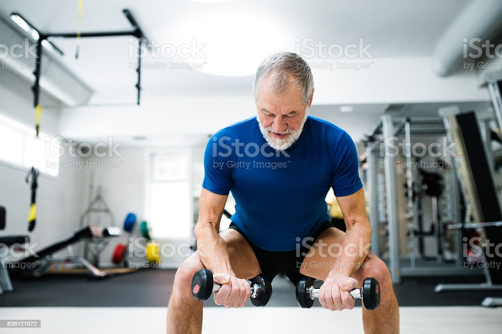 Senior man in gym working out with weights, squatting. stock photo