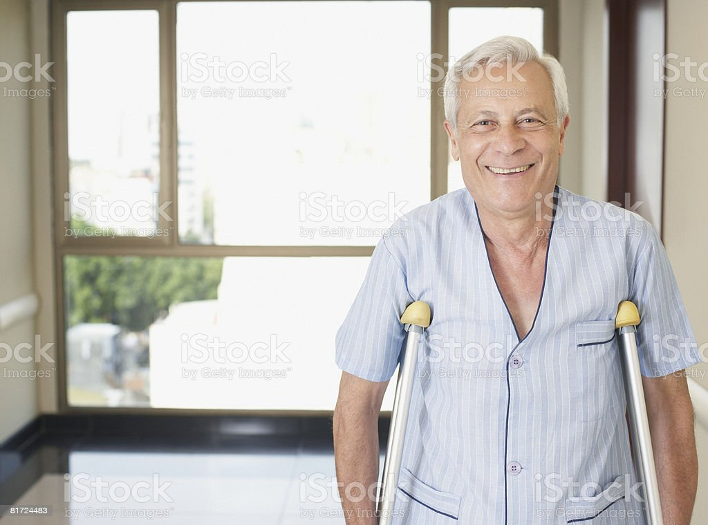 Senior man in hospital corridor using crutches and smiling royalty-free stock photo