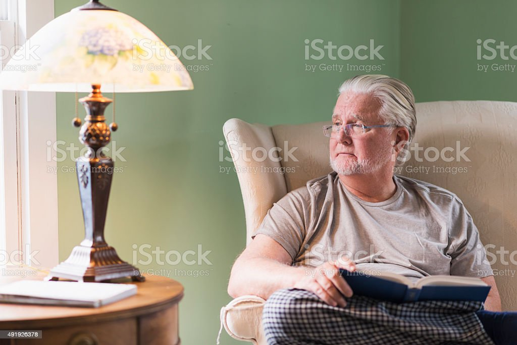 Senior man in living room reading book stock photo