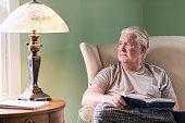 Senior man in living room reading book