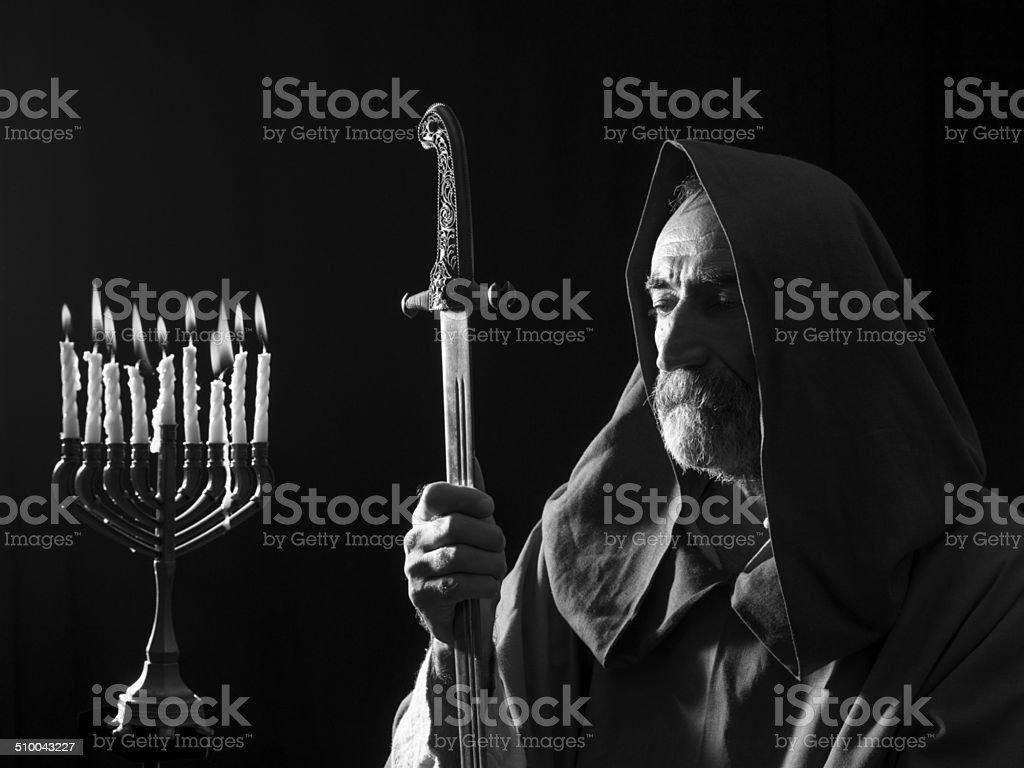 Senior man in medieval costume under the light of menorah stock photo