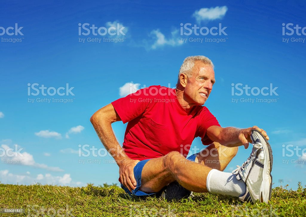 Senior Man In Pain While Stretching Leg On Meadow stock photo