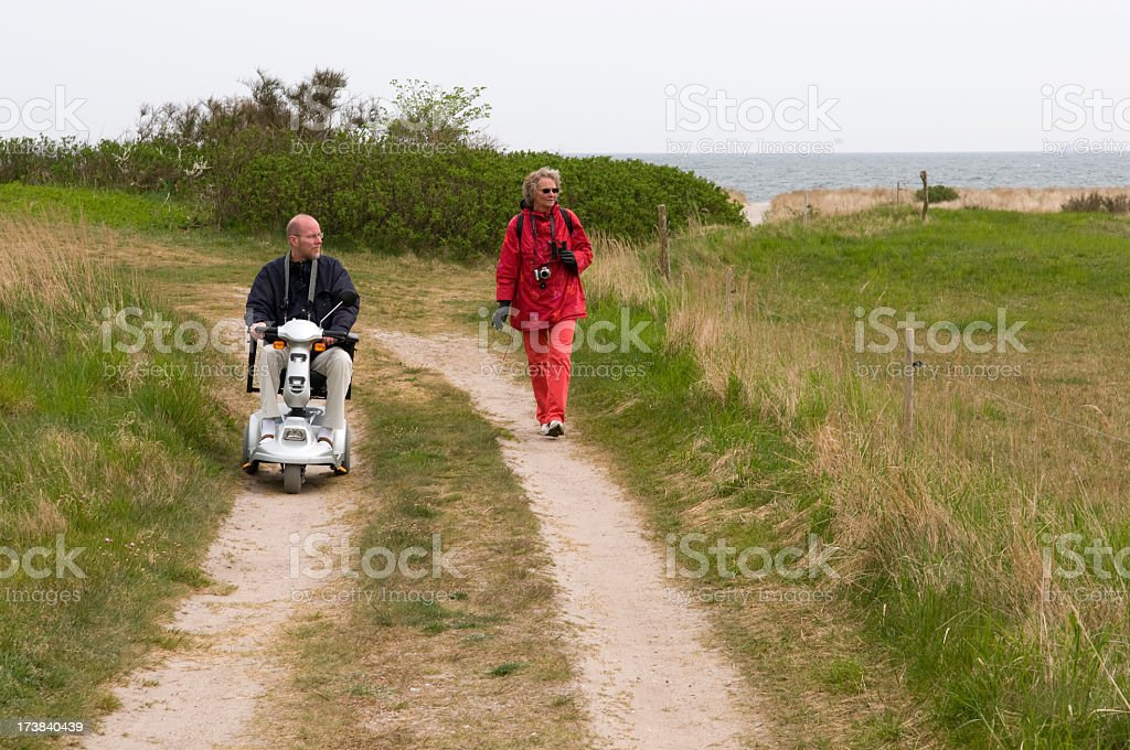 Senior man in scooter and woman walking on nature path stock photo