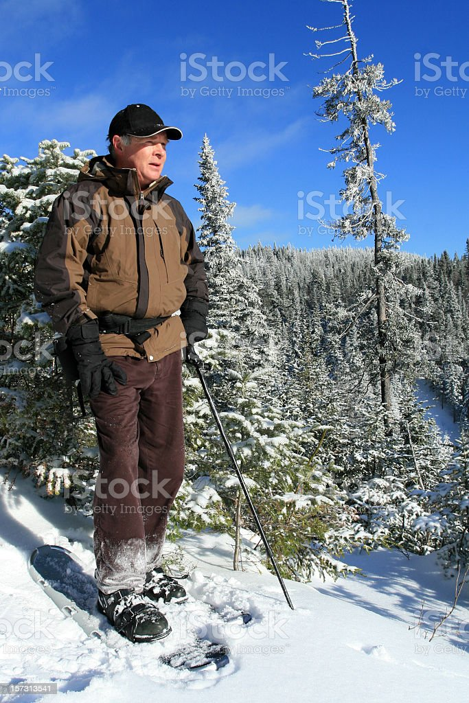 Senior Man in Snowshoe Trail Loking at the View stock photo