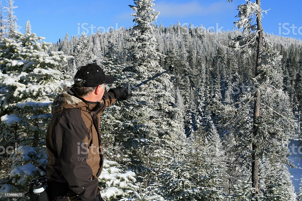 Senior Man in Snowshoe Trail Pointing a Direction stock photo