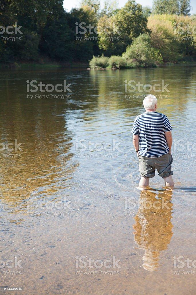 senior man in striped t-shirt paddles in sunny river stock photo