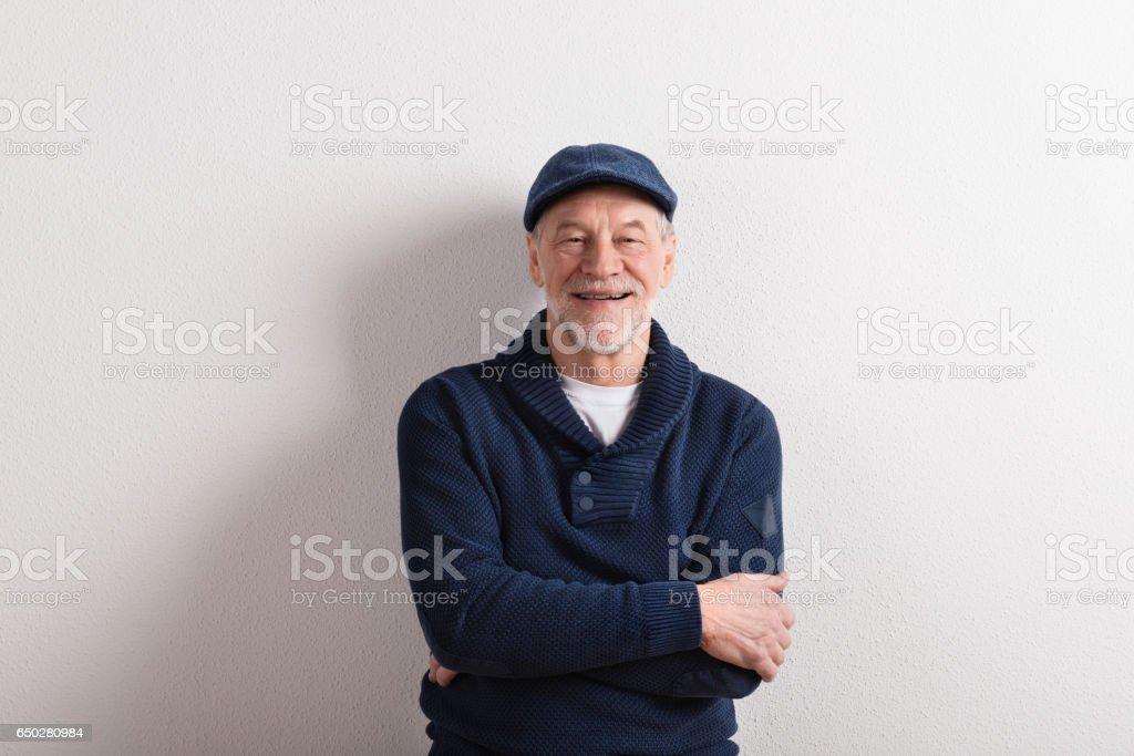 Senior man in sweater and cap, studio shot. stock photo