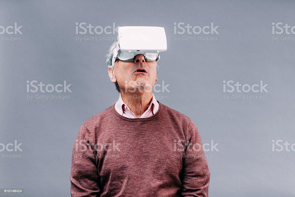 Senior man in virtual reality experience stock photo