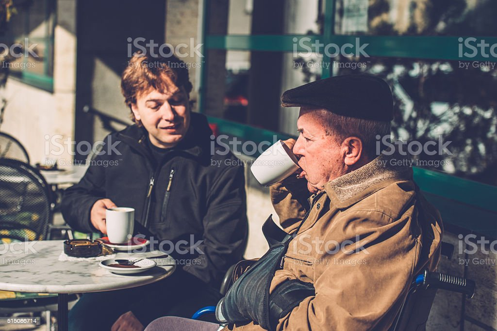 Senior Man in Wheelchair and Grandson Having Coffee, Europe stock photo