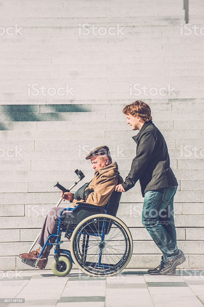 Senior Man in Wheelchair and Grandson in the City, Europe stock photo