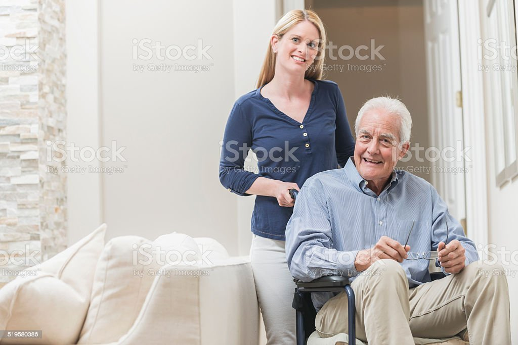 Senior man in wheelchair with caregiver at home stock photo