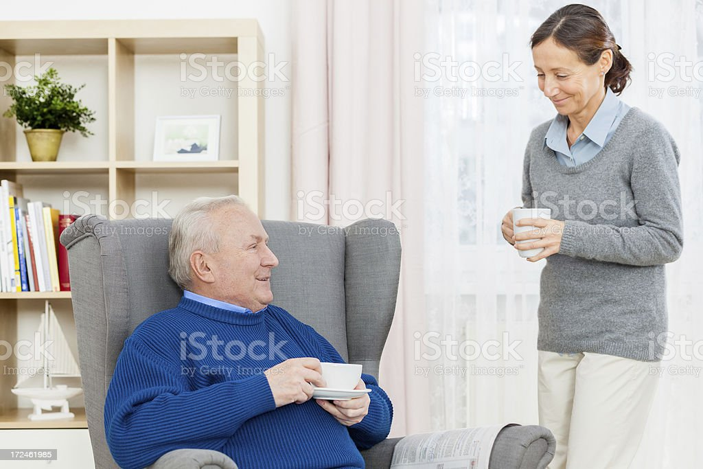 Senior Man In Wing Chair with Caregiver royalty-free stock photo