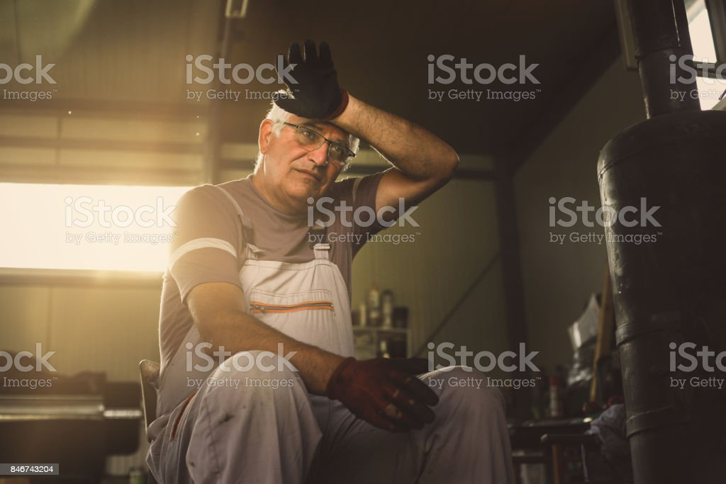 Senior man in workshop. Man sits next to the furnace and heats up. stock photo