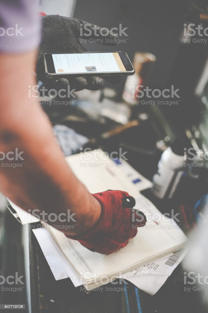 Senior man in workshop. Man writing obligations in his notes and using smart phone. Close up. stock photo