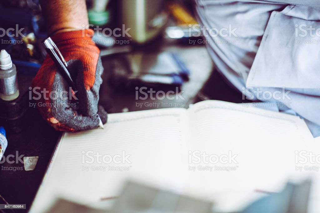 Senior man in workshop. Man writing obligations in his notes. Close up. stock photo