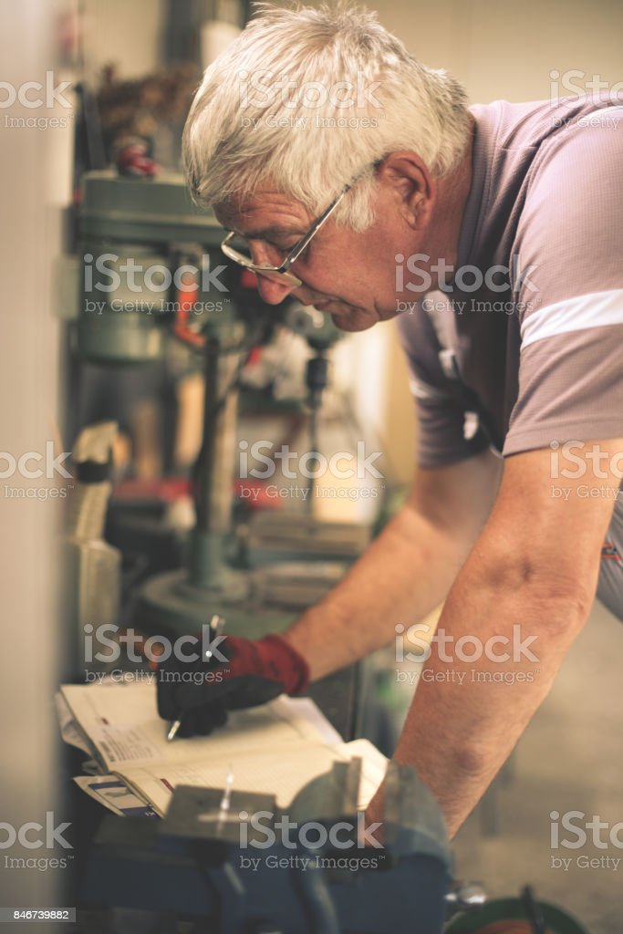 Senior man in workshop. Man writing obligations in his notes. stock photo