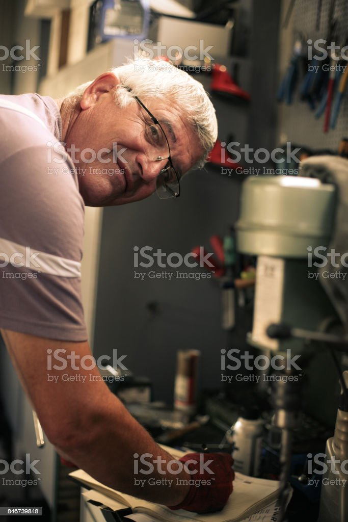 Senior man in workshop. Smiling man writing obligations in his notes. Looking at camera. stock photo