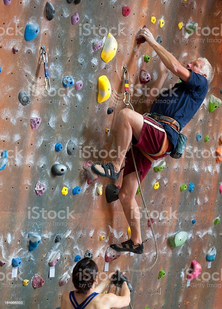 Senior Man Indoor Rock Climbing stock photo