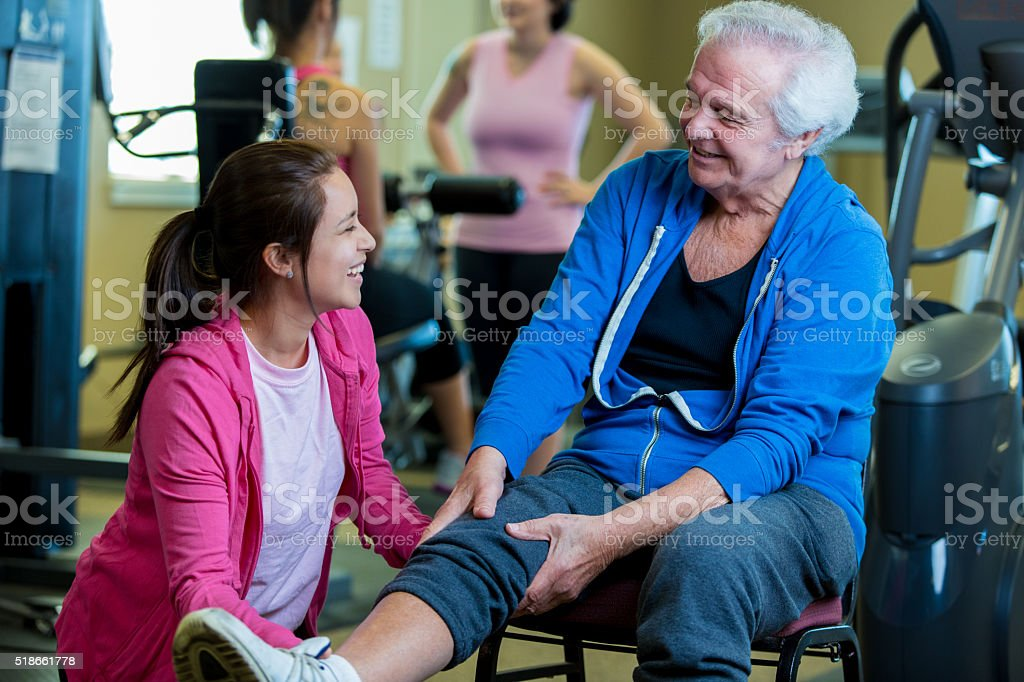 Senior man is evaluated by physical therapist stock photo