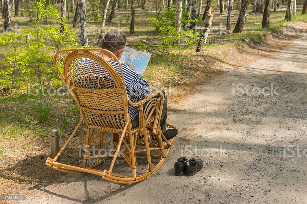 Senior man is having rest in coniferous forest stock photo