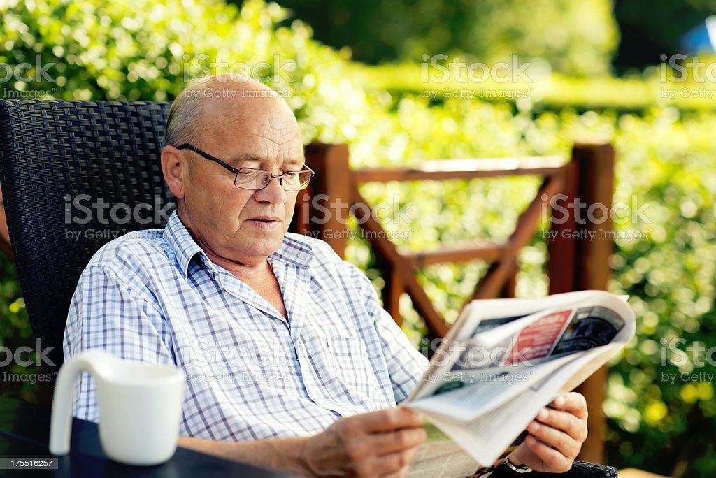 Senior man is reading a newspaper outside royalty-free stock photo