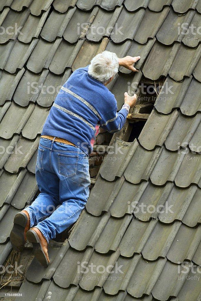 Senior man is reparing roof royalty-free stock photo