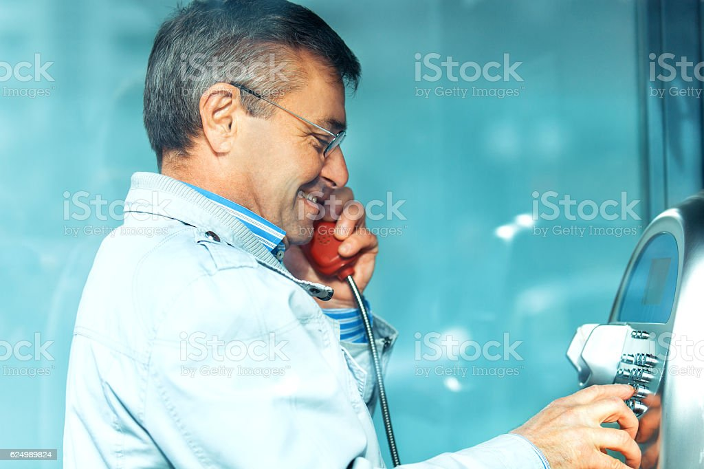 Senior man is talking telephone booth stock photo