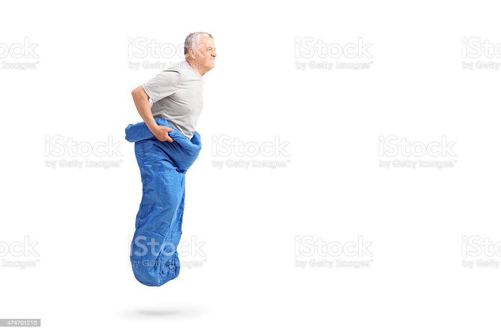 Senior man jumping in a blue sack and smiling stock photo