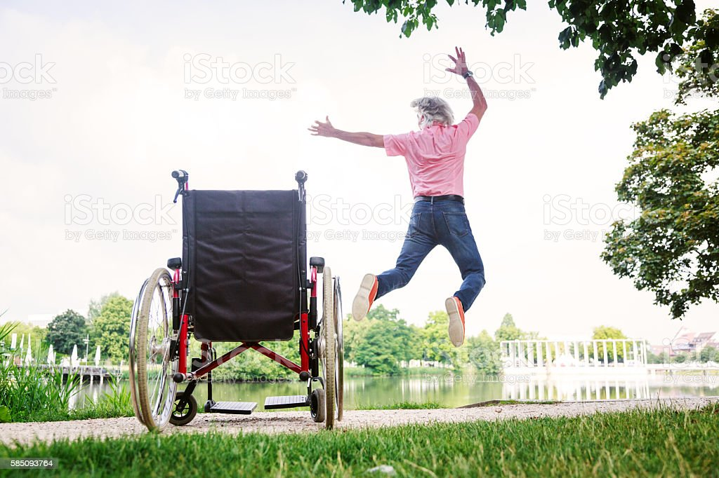Senior man jumping up from his wheelchair stock photo