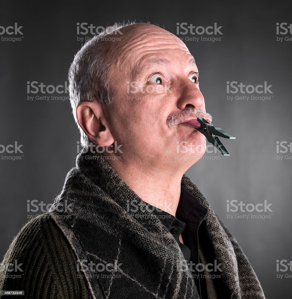 Senior man keeping silence with closed mouth by clothespin stock photo