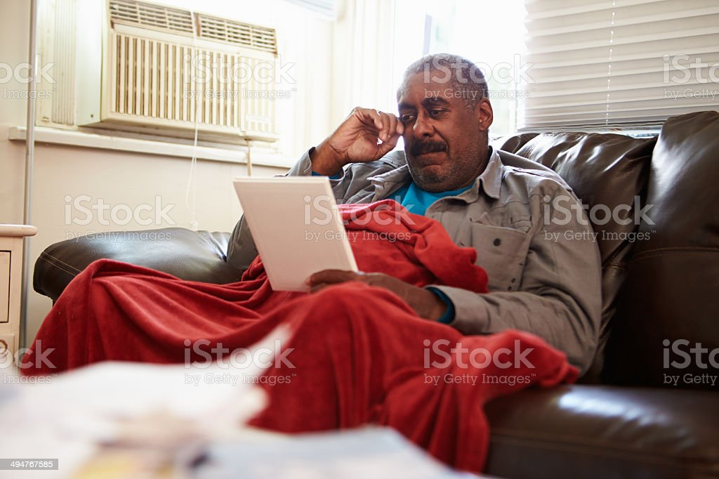 Senior Man Keeping Warm Under Blanket With Photograph stock photo