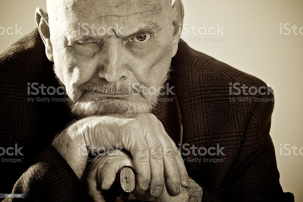 Senior Man Leaning Head on His Cane, Sepia Toned stock photo