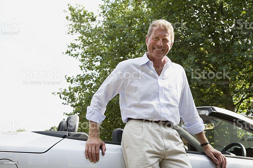 Senior man leaning on convertible stock photo