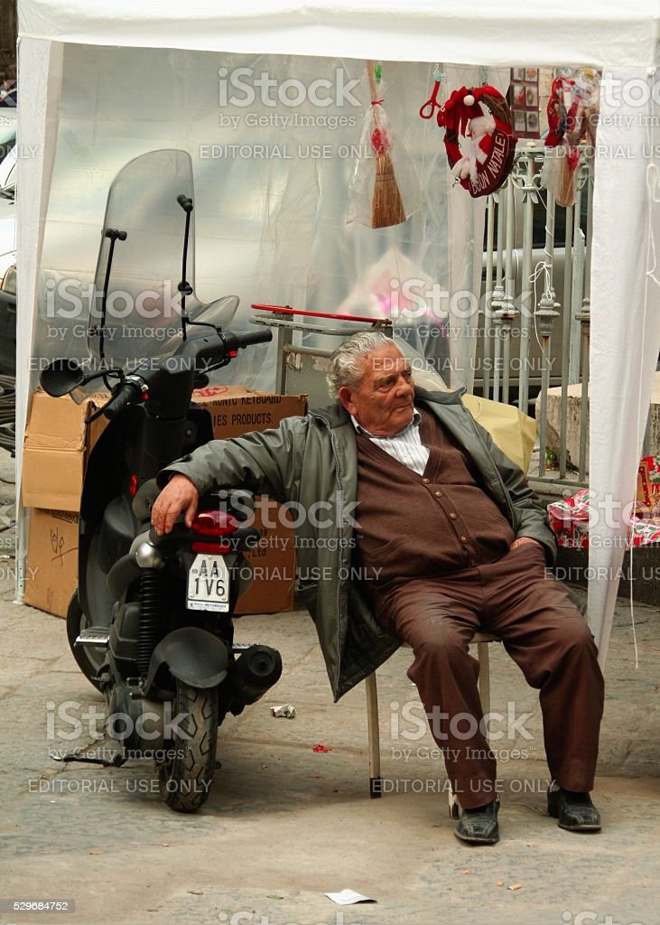 Senior man leaning on his moto scooter Naples real life stock photo