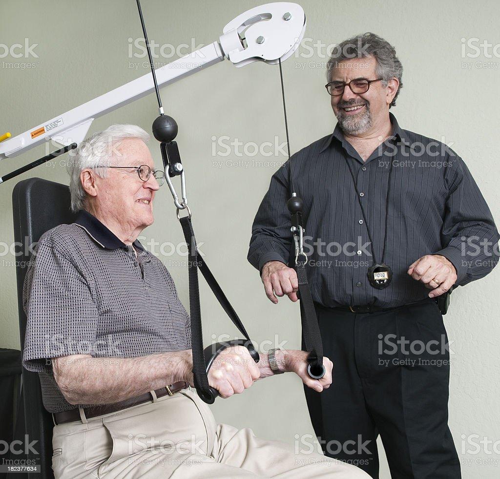 Senior Man Learning Arm Exercises on Weight Machine royalty-free stock photo