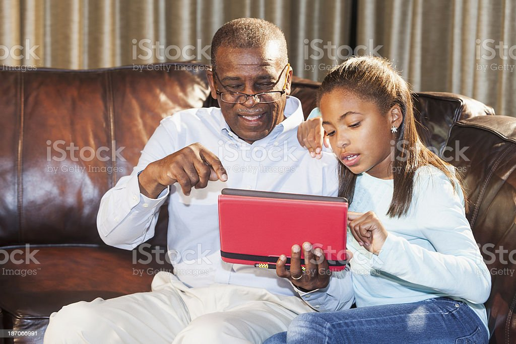 Senior man learning from grandchild how to use digital tablet stock photo